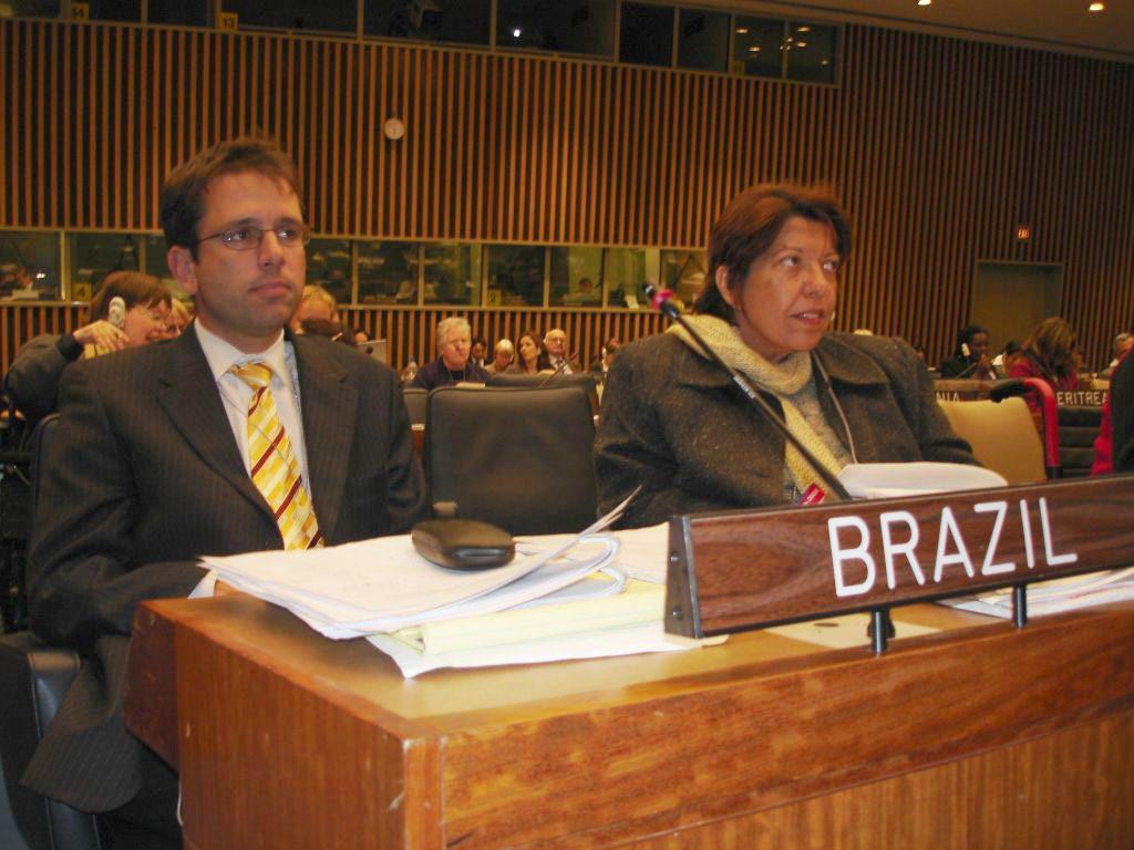 """Em plenário da ONU, Izabel Maior e Pedro Cardoso olhampara frente. Em mesa, livros abertos e placa em que se lê """"Brazil"""". Fim da descrição."""