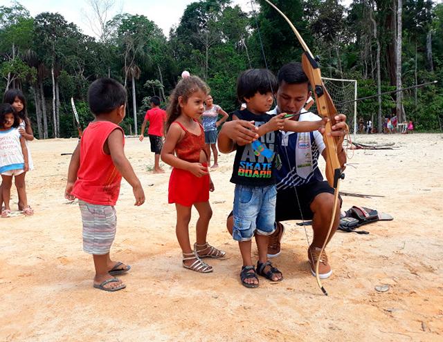 Em campo aberto, cercados por outras crianças, menino tem auxílio de um adulto para segurar um arco e flecha. Uma menina observa. Fim da descrição.