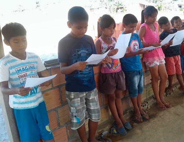 Em pé, uma ao lado da outra, crianças seguram uma folha de papel e prestam atenção em seu conteúdo. Fim da descrição.