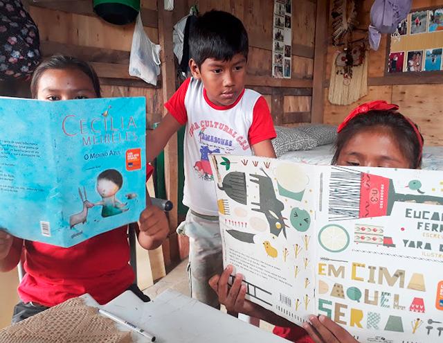 No CMEEI, duas crianças estão sentadas, lendo livros. Um menino as observa, de pé. Fim da descrição.
