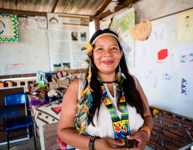 No CMEEI, Claudia Baré, utilizando tiara e colar de penas e colar e pulseira coloridos, sorri para a foto. Fim da descrição.