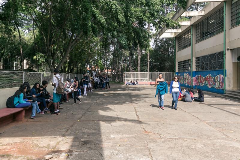 Em pátio de escola, vários estudantes se reúnem em volta de acentos,enquanto alguns estão sentados no chão e outros caminham. Fim da descrição.