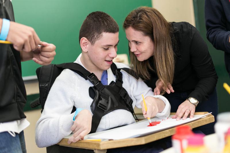 Em sala de aula, estudante em cadeira de rodas pinta em cartolina com pincel. Ao seu lado e debruçada sobre mesa de apoio, educadora sorri enquanto olha para ele. Fim da descrição.