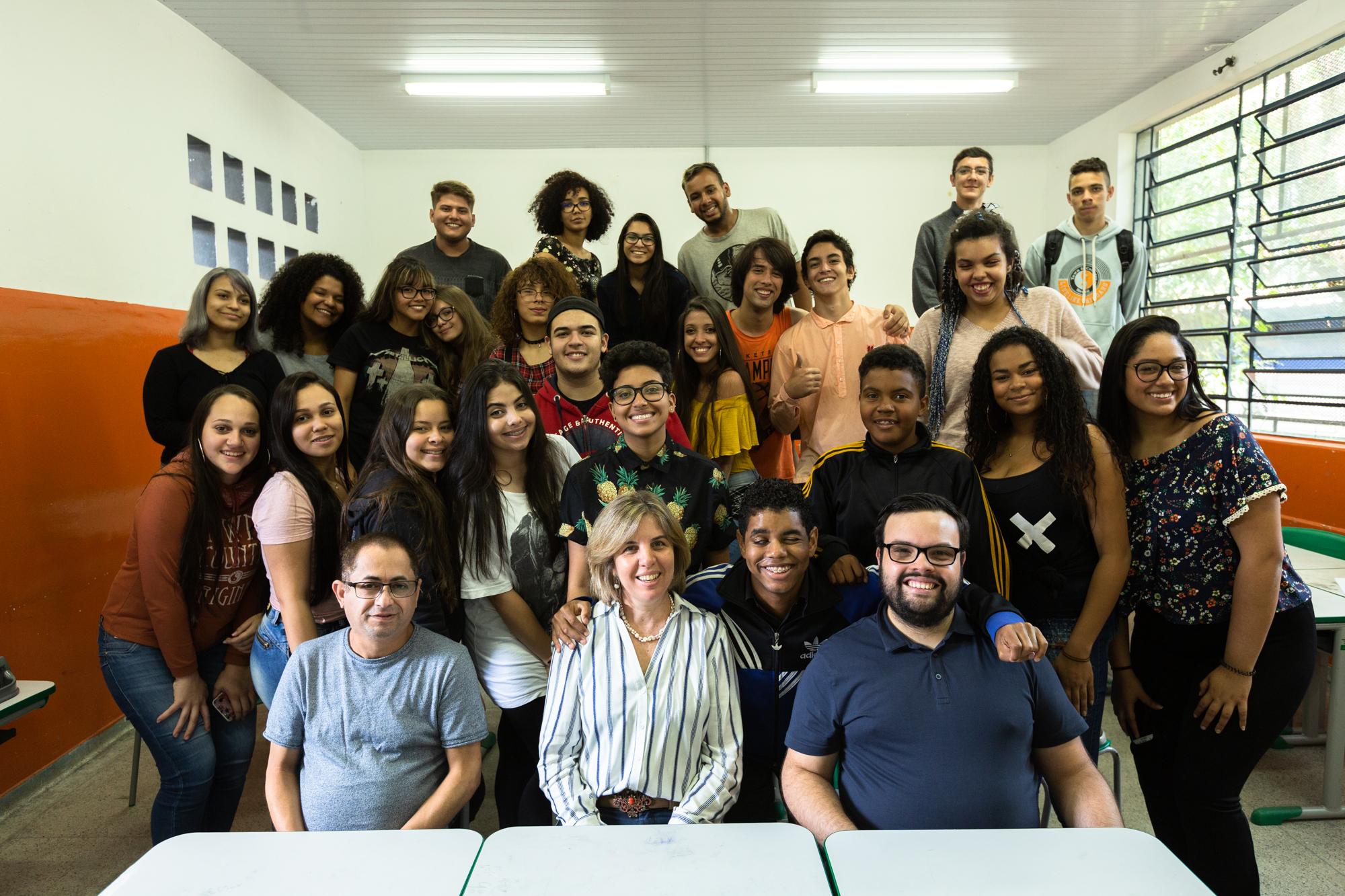 Em sala de aula, grupo de estudantes e professores posam para foto em fileiras. Os da frente estão sentados; enquanto os de trás, em pé.