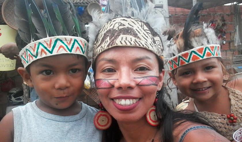 Um menino e uma menina, com Vanda ao centro, sorriem para a câmera. Todos usam um adorno com penas e pinturas na cabeça. Vanda está com uma pintura vermelha nas bochechas. Fim da descrição.