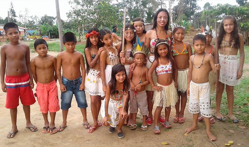 Vanda Witoto e 14 crianças posam para foto. Alguns estão com roupas e pinturas tradicionais indígenas. Fim da descrição.