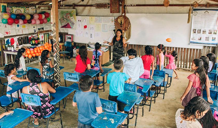 No CMEEI, Claudia está de frente para várias crianças, que estão de pé ao lado de carteiras escolares. No lado esquerdo do espaço de aulas, há bexigas coloridas sobre mesa e na parede. Fim da descrição.