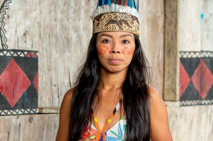 Vanda Witoto, em frente à estrutura de madeira, olha para a câmera. Ela usa cocar, colar colorido e pintura tradicional no rosto. Fim da descrição.