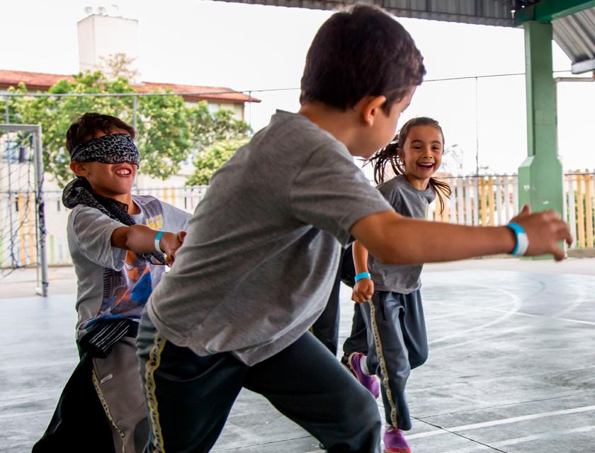 Em quadra escolar, três estudantes correm de mãos dadas. Um deles usa vendas nos olhos e dois sorriem. Fim da descrição.