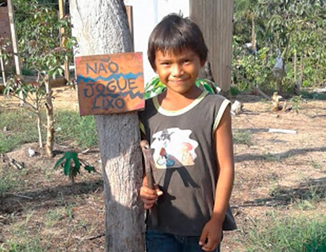 """Em área verde, menino sorri ao lado de uma placa pintada a mão, onde se lê: """"não jogue lixo"""". A placa está pendurada em uma árvore. Fim da descrição."""