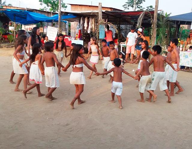 Em espaço aberto, Vanda participa de roda de dança onde crianças estão de mãos dadas. Todos vestem roupas claras. Alguns estão com pinturas no rosto. Fim da descrição.