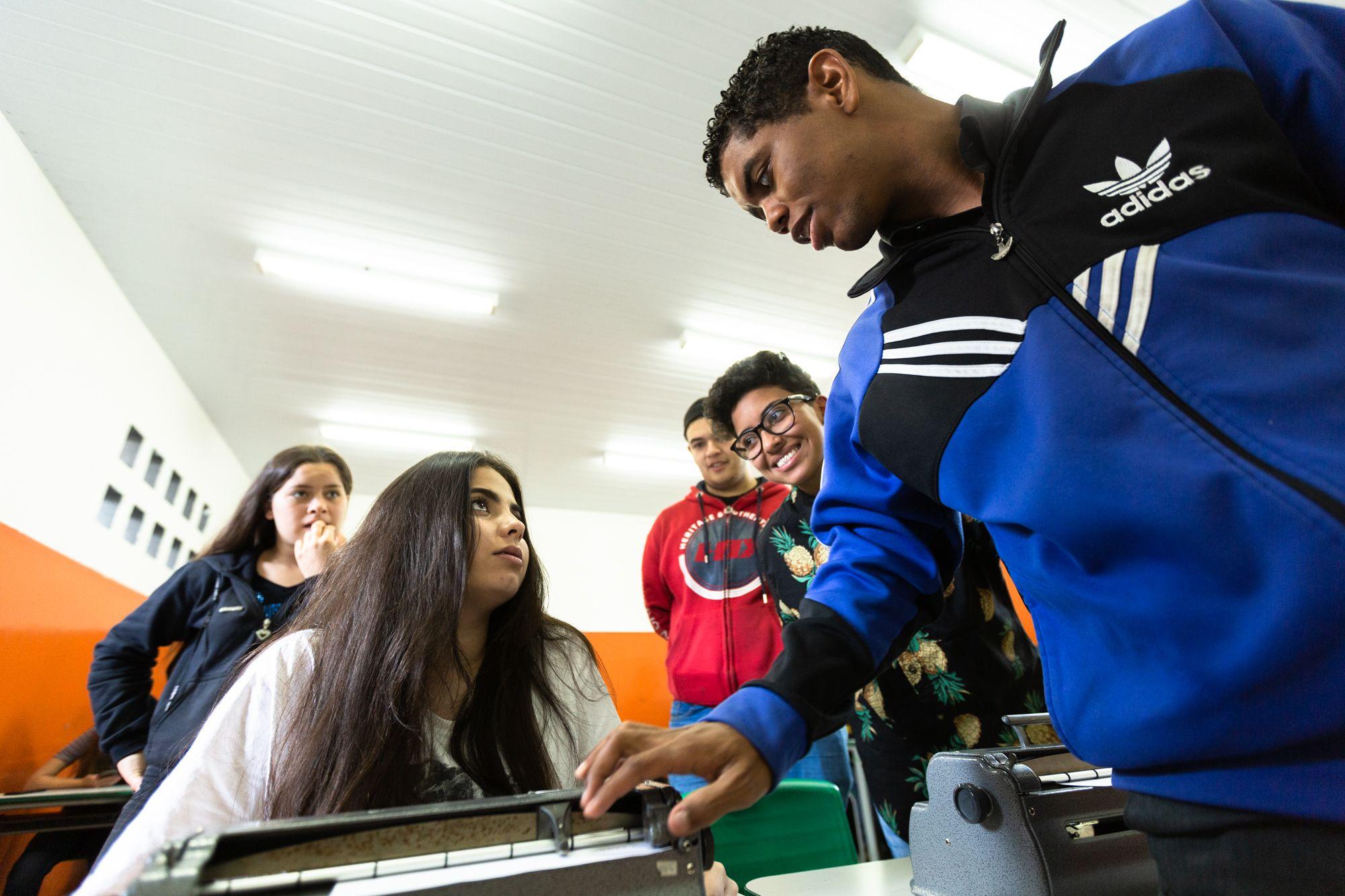Em sala de aula, estudante orienta colega a escrever em máquina braile, enquanto é observado por outros três alunos. Fim da descrição.