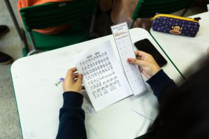 Sobre carteira escolar, estudante segura com as mãos filipeta com alfabeto em braile. Fim da descrição.