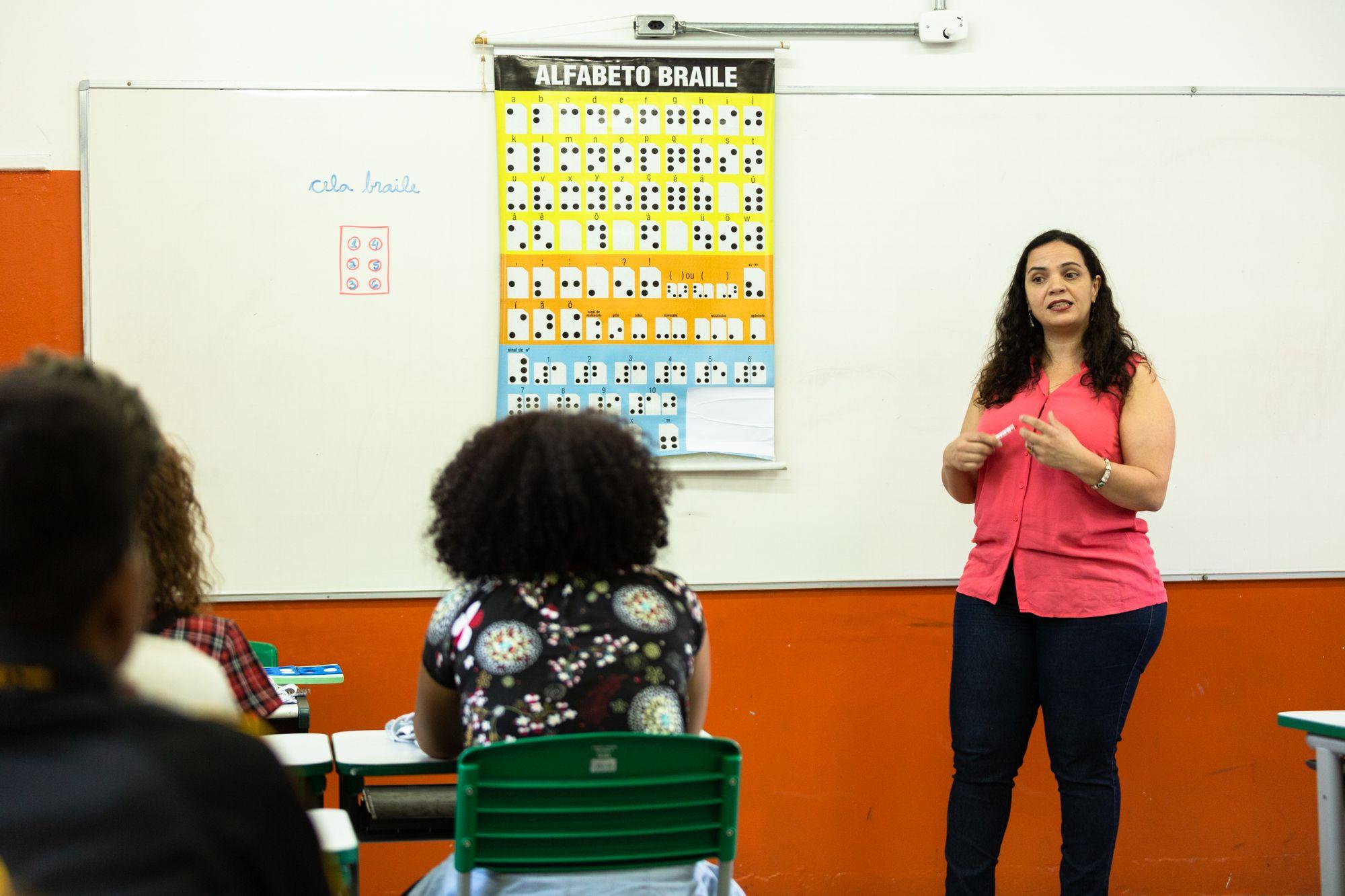 Em sala de aula, educadora fala a alunos em frente à lousa com cartaz do alfabeto em braile. Fim da descrição.