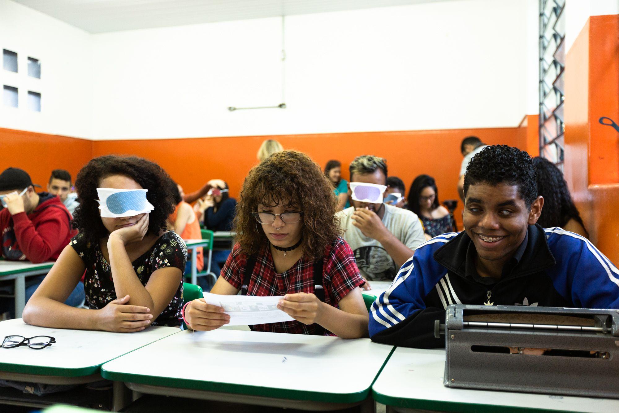 Em sala de aula, alguns estudantes estão com os olhos vendados. Em primeiro plano, aluna sentada em carteira escolar segura folha em suas mãos. Ao seu lado, estudante co deficiência visual sorri. Sobre a sua carteira está uma máquina de escrever em braile.