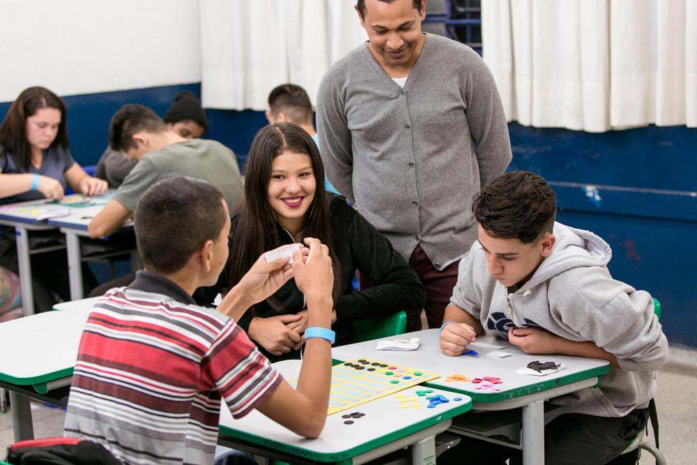 Em sala de aula, professor Kleberson sorri enquanto observa uma menina e dois meninos sentados em volta de mesa, interagindo com Jogo de senhas. A menina também sorri. Fim da descrição.