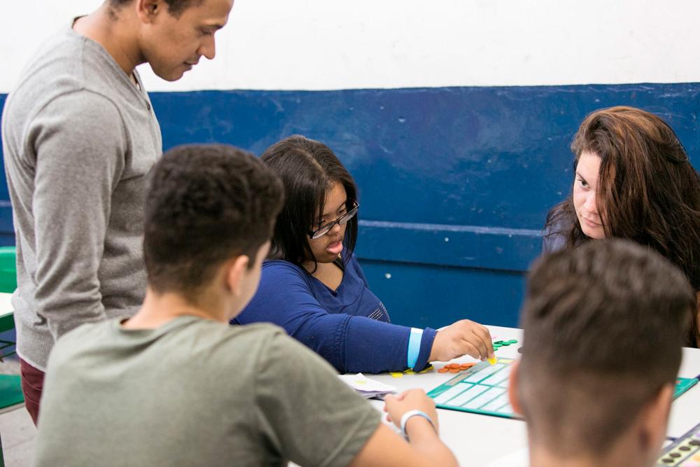 Em sala de aula, professor acompanha envolvimento de duas meninas e dois meninos com o material pedagógico. Ester posiciona peça amarela de EVA em tabuleiro. Fim da descrição.