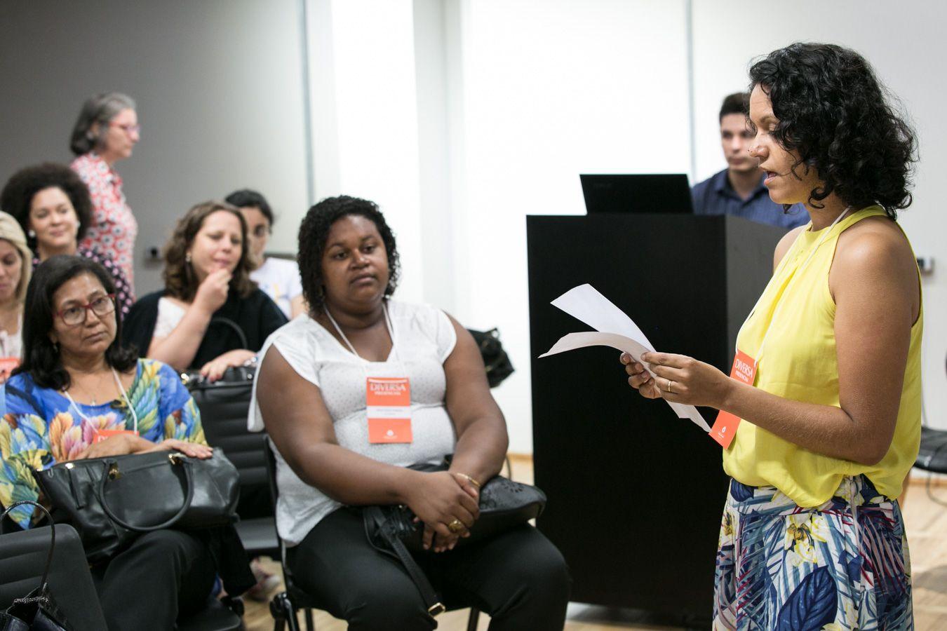 Em auditório, educadora, em pé, lê folha em suas mãos. Ao redor, mulheres sentadas em cadeiras a observam. Fim da descrição