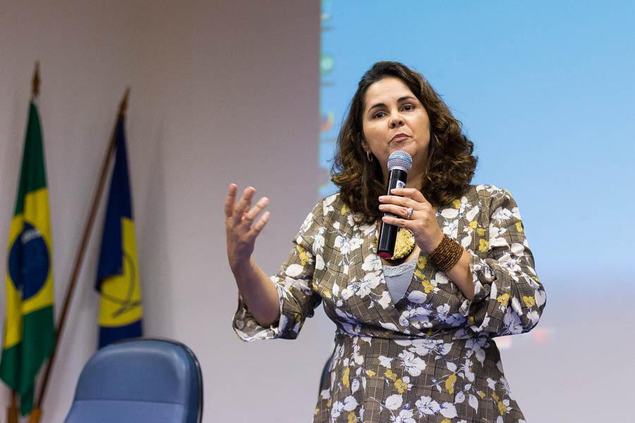 Em auditório, Eugênia gesticula segurando um microfone em sua mão esquerda. Ao fundo bandeira do Brasil em mastro. Fim da descrição.