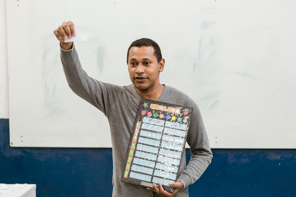 De frente para lousa branca, professor apresenta o placar de pontuação do jogo das senhas. Fim da descrição.