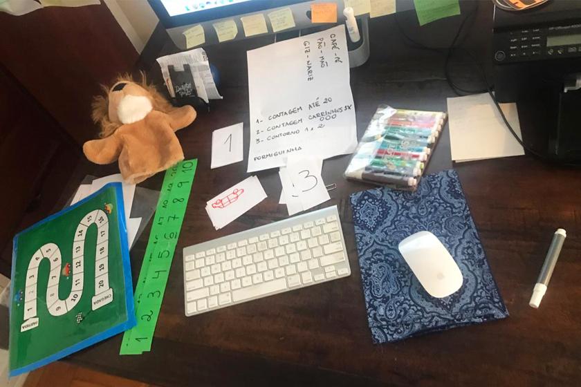 """Sobre mesa de madeira, estão materiais de aula como canetas colorida; fantoche de leão; teclado e mouse de computador; recortes de papel com números e carros desenhados; tiras em papel verde com numeração do um ao vinte; tabuleiro de jogo em verde; anotações em post-it; e uma folha de sulfite com os textos: """"1 - contagem do 1 ao 20""""; """"2 - contagem carrinhos""""; """"3 - contorno um e dois"""" e """"Formiguinhas"""". Fim da descrição."""