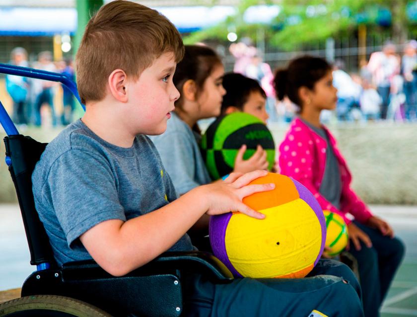Em quadra escolar, quatro estudantes estão perfilados e olham para frente. Três deles seguram bolas de diferentes esportes em suas mãos. Em primeiro plano, aluno está sentado em cadeira de rodas. Fim da descrição.