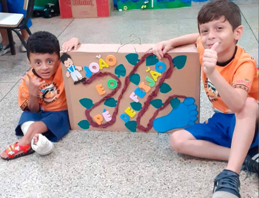 """Em sala de aula, estudantes posam para foto sorridentes segurando caixa de papelão pintada com uma trilha e folhas e uma marca de pegada. Na caixa encontra-se inscrita a frase: """"João e o pé de feijão"""". Fim da descrição."""