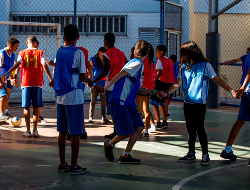 Em quadra escolar, estudantes se dividem entre grupos de colete azul e colete laranja. Os grupos estão de mãos dadas e em fileiras Todos olham atentos em direção a uma bola de futebol dominada por um dos alunos e próxima a um dos gols. Fim da descrição.