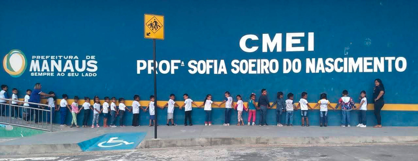 Em frente a fachada do CMEI Profª Sofia Soeiro do Nascimento, estudantes caminham em linha de mãos dadas, orientadas por educadoras. Fim da descrição.