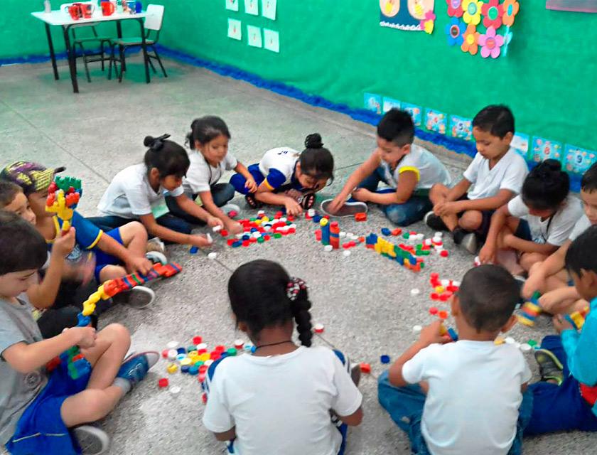 Em sala de aula, estudantes brincam com peças de lego reunidos em uma grande roda. Fim da descrição.