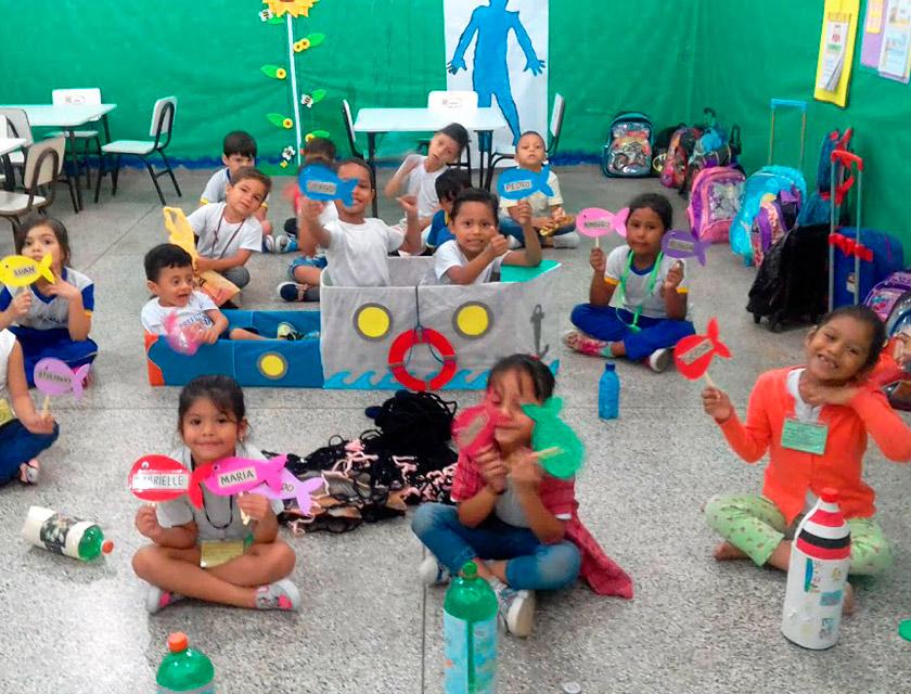 Em sala de aula, crianças seguram componentes de materiais reciclados, como papelão, palitos e garrafas pet. Fim da descrição.