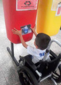 Em pátio escolar, aluno em cadeira de rodas, cola imagem de lixeira reciclável azul em lixeira vermelha para plásticos. Fim da descrição.