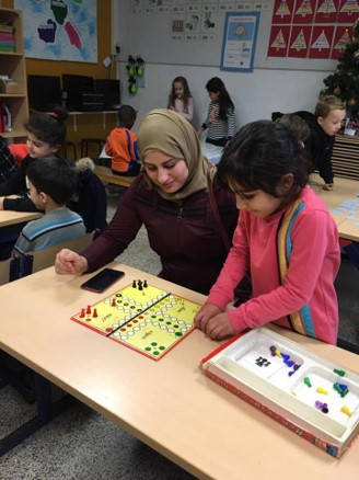 Em sala de aula, educadora com hijab na cabeça está acompanhando um jogo de tabuleiro com aluna. Ao fundo, diversas crianças realizam outras atividades. Fim da descrição.