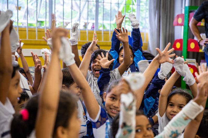 Em sala de aula, estudantes levantam as mãos e sorriem. Todos usam as luvas da Cartola mágica em uma das mãos. Fim da descrição.