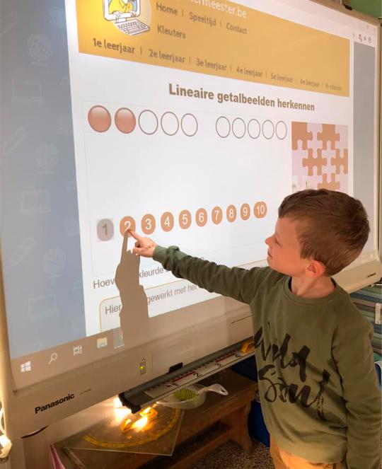 Em sala de aula, há uma apresentação projetada em tela, com números do 1 ao 10. Menino olha a projeção e aponta para o número 2. Fim da descrição.
