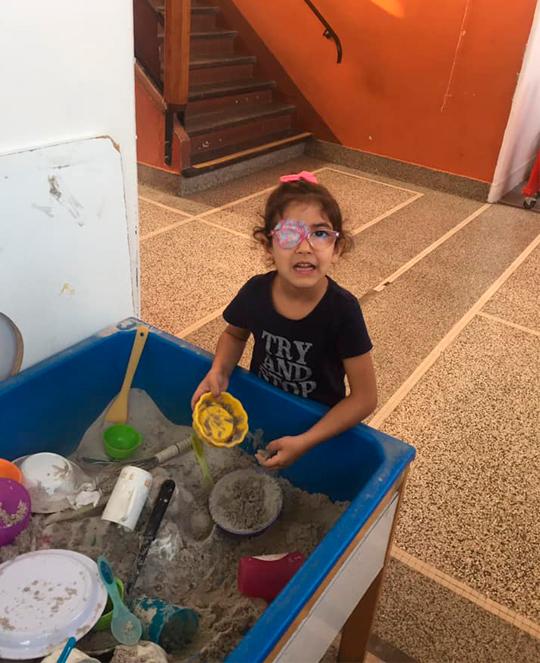 Menina pega brinquedos em caixa de areia. Fim da descrição.