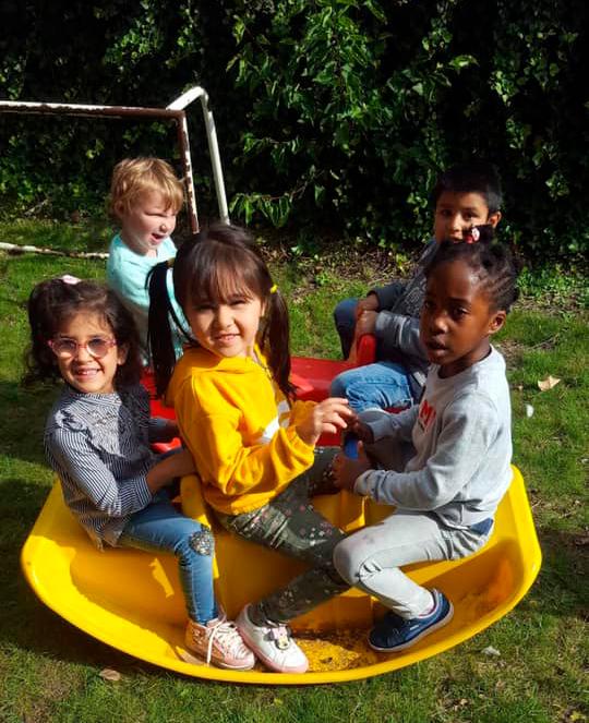 Três meninas brincam sentadas em brinquedo de balança do parquinho. Ao fundo, dois meninos estão sentados em outro brinquedo. Fim da descrição.