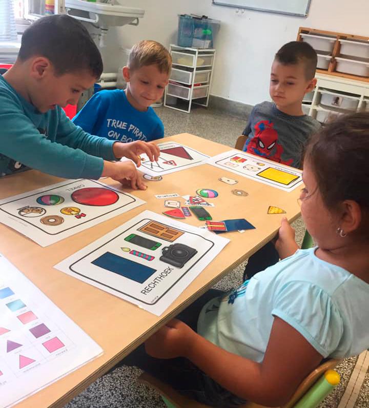 Em sala de aula, três meninos e uma menina estão sentados em volta de mesa, realizando atividades com formas geométricas. Fim da descrição.
