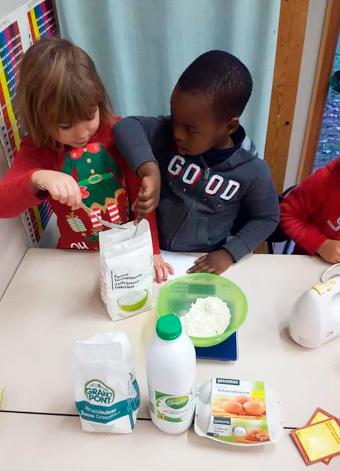 Em sala de aula, menina e menino pegam farinha de saco com uma colher cada um. Sobre a mesa, há uma tigela verde com farinha e embalagens de ovos, leite, e açúcar. Fim da descrição.