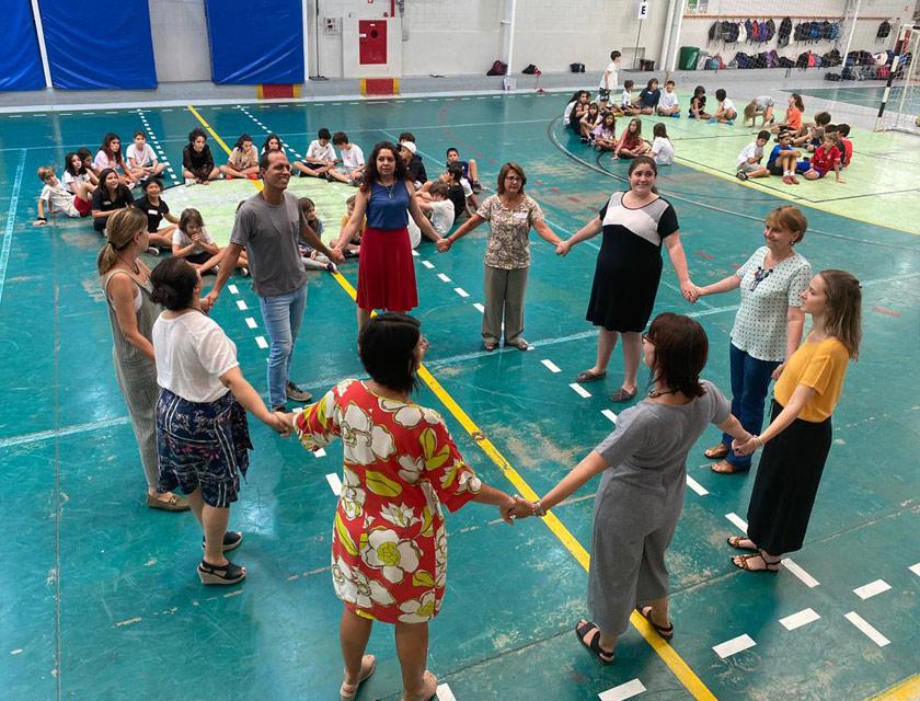 Em quadra esportiva, educadores fazem círculo de pé e de mãos dadas. Em outros espaços da quadra, estudantes estão sentados em círculos no chão. Fim da descrição.