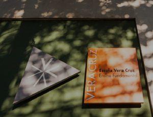 """Fachada da escola Vera Cruz. Em cinza, forma de triângulo com símbolo de asterisco em branco. Ao lado, retângulo laranja com textos """"Escola Vera Cruz"""" e """"Ensino Fundamental"""". Fim da descrição."""