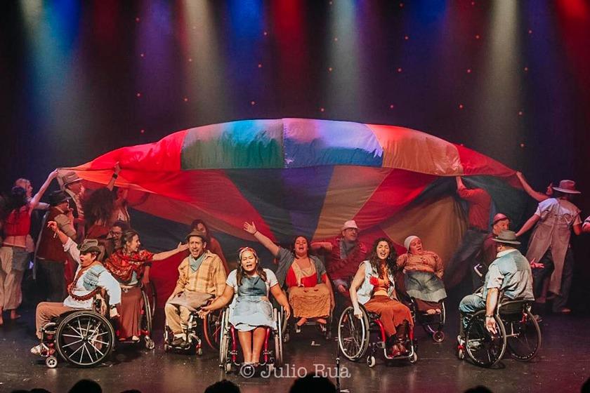 Em palco, elenco de grupo teatral segura em semicírculo grande lona com cores em gradação. Alguns estão em cadeiras de roda e outros em pé. Fim da descrição.