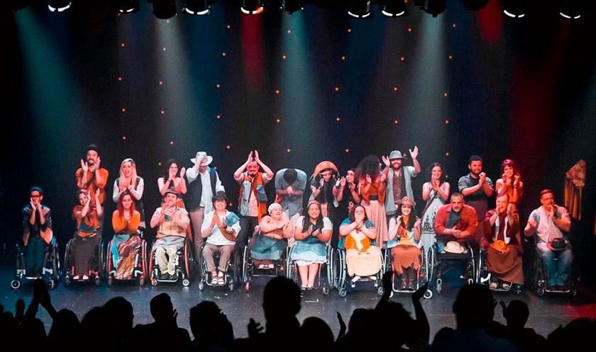 Em palco, elenco de grupo teatral bate palmas. Há pessoas em pé e outras em cadeiras de rodas. À frente deles, silhueta de público aplaudindo. Fim da descrição.