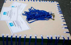 Medalhas e certificados espalhados sobre mesa. Fim da descrição.