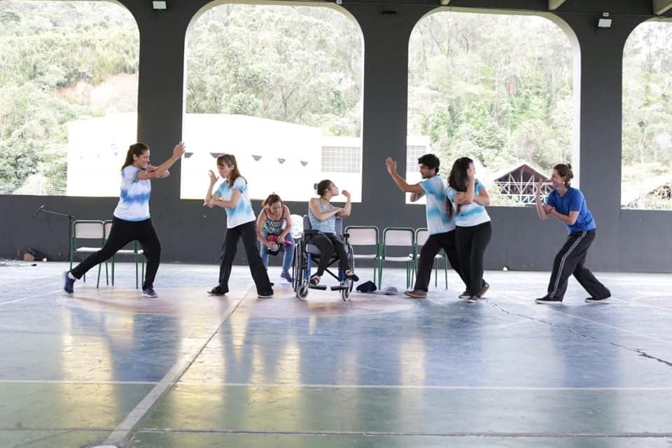 Em quadra esportiva, estudantes realizam movimentos de dança. Ao centro, uma das alunas está em cadeira de rodas. Fim da descrição.