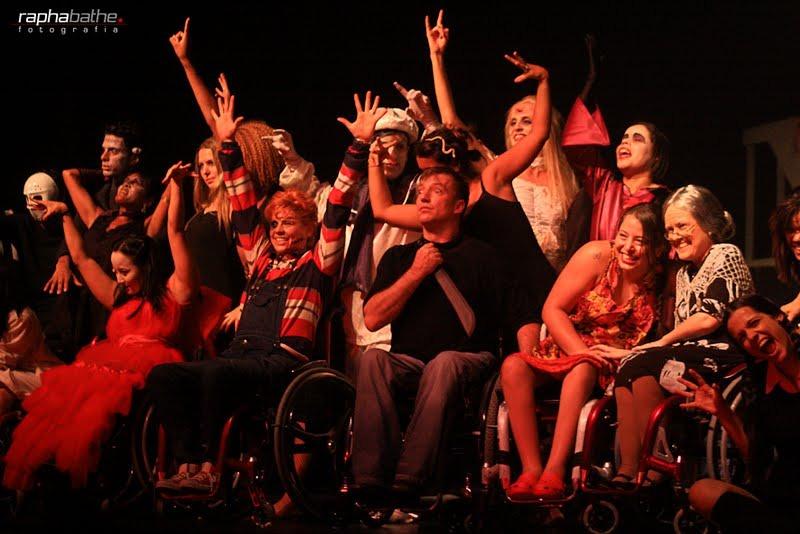 Em palco, pessoas em pé e em cadeiras de rodas atuam com fantasias de dia das bruxas. Fim da descrição.