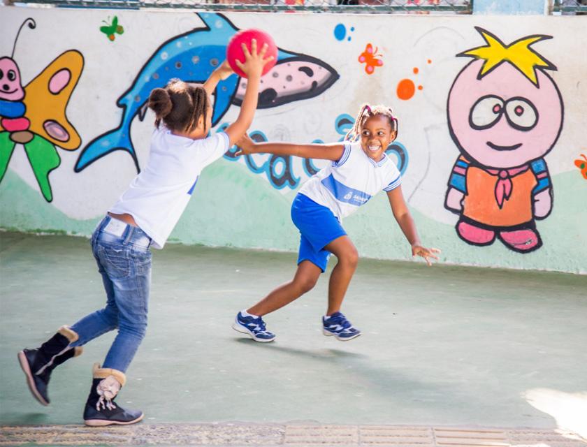 Em pátio escolar, duas alunas uniformizadas correm. Uma delas segura uma bola vermelha com as duas mãos levantadas acima da altura da cabeça, enquanto a outra sorri. Ao fundo, um muro com ilustrações coloridas de uma borboleta, um tubarão e de uma criança. Fim da descrição.
