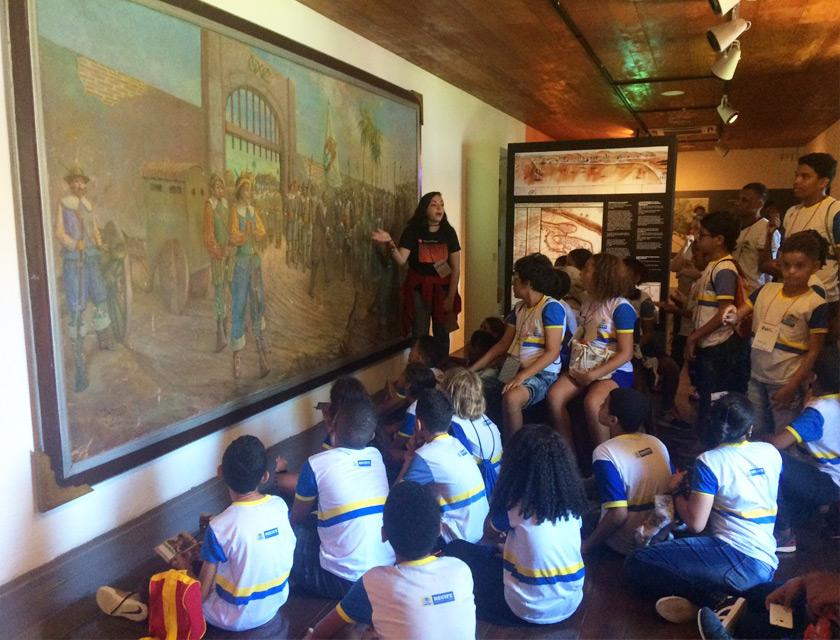 Em museu, estudantes se reúnem em frente a um quadro, alguns estão sentados no chão e outros em pé. Eles observam atentos a educadora, que está de pé ao lado do quadro. Fim da descrição.