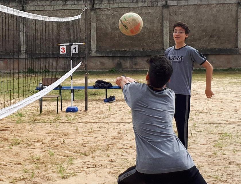 Em quadra de areia, dois estudantes uniformizados jogam vôlei. Em frente à uma rede, um dos estudantes faz movimento de manchete, enquanto o outro aluno observa atento. Fim da descrição.