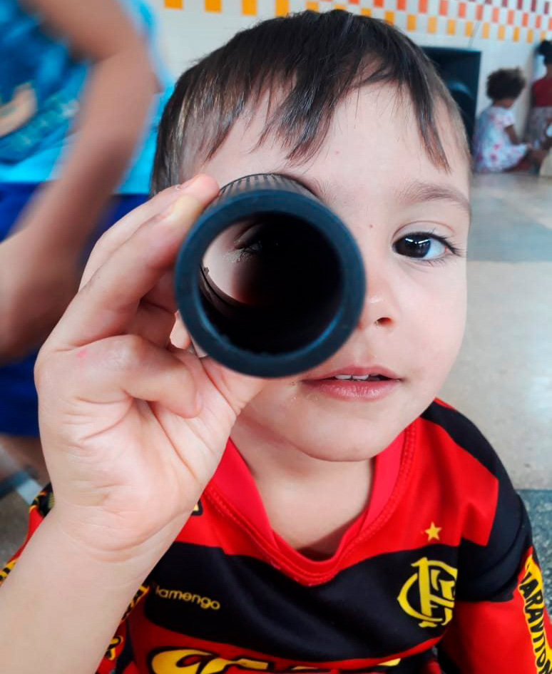 Em pátio escolar, criança com a camisa do Flamengo apoia tubo vazado em seu rosto com a mão direita, criando uma experiência de monóculo. Fim da descrição.